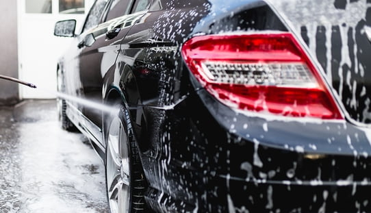 cleaning a car with a high pressure spray